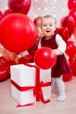 Concepto del día de tarjeta del día de San Valentín - retrato del bebé divertido con los globos rojos y el regalo grande foto de archivo