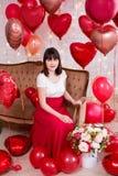 Concepto del día de tarjeta del día de San Valentín - retrato integral de la mujer joven que se sienta en el sofá del vintage con fotos de archivo