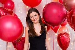 Concepto del día de tarjeta del día de San Valentín - retrato de la mujer hermosa en negro con los balones de aire rojos fotografía de archivo libre de regalías