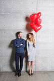 Concepto del día de tarjetas del día de San Valentín El par cariñoso con el corazón rojo hincha en fondo gris foto de archivo