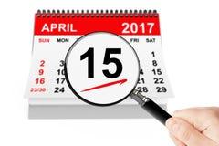 Concepto del día del impuesto 15 de abril de 2017 calendario con la lupa Foto de archivo