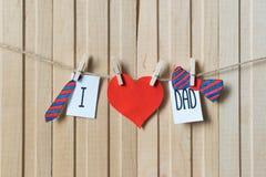 Concepto del d?a de padres Mensaje con los corazones, el lazo de papel y la corbata de lazo colgando con los pernos sobre el tabl foto de archivo libre de regalías