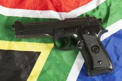 Concepto del delito violento con una arma de mano y una bandera surafricana fotografía de archivo libre de regalías