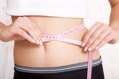 Concepto del deporte, de la aptitud y de la dieta - primer del vientre entrenado con la cinta métrica Imagenes de archivo