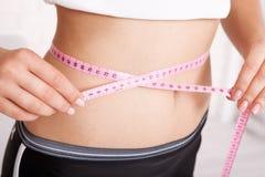 Concepto del deporte, de la aptitud y de la dieta - primer del vientre entrenado con la cinta métrica Foto de archivo