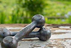 Concepto del deporte y de la aptitud Ciérrese encima de la imagen de la pesa de gimnasia del vintage que miente en la tabla de ma Foto de archivo libre de regalías