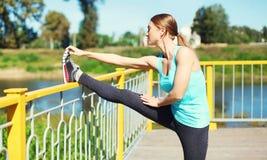 Concepto del deporte y de la aptitud - mujer que hace estirando ejercicio en ciudad Fotografía de archivo