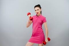Concepto del deporte y de la reconstrucción - manos deportivas de la mujer con pesas de gimnasia rojas claras Muchacha bonita en  imagen de archivo