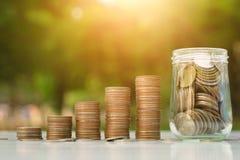 Concepto del dinero del ahorro con el crecimiento de la pila de la moneda y negocio de la botella en fondo de la puesta del sol fotografía de archivo