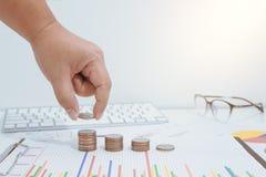 Concepto del dinero del ahorro preestablecido por la mano masculina que pone el stac de la moneda del dinero Fotos de archivo libres de regalías
