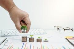 Concepto del dinero del ahorro preestablecido por la mano masculina que pone el stac de la moneda del dinero Foto de archivo libre de regalías