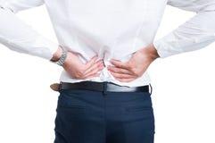Concepto del dolor de espalda con el hombre de negocios que lleva a cabo las manos en más de espalda Fotos de archivo
