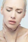 Concepto del dolor Mujer joven con el tacto de su garganta Fotos de archivo libres de regalías