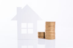 Concepto del domicilio familiar del anuncio de negocio y moneda creciente de la pila Foto de archivo
