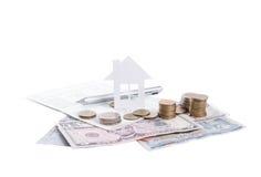 Concepto del domicilio familiar del anuncio de negocio y moneda creciente de la pila Foto de archivo libre de regalías