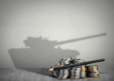 Concepto del ejército del financiamiento, dinero con la sombra del arma foto de archivo