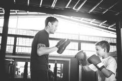 Concepto del ejercicio de los mitones del sacador del entrenamiento del boxeo del muchacho fotografía de archivo