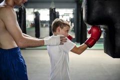 Concepto del ejercicio del saco de arena del entrenamiento del boxeo del muchacho fotografía de archivo libre de regalías