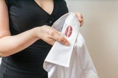 Concepto del engaño y de la infidelidad La mujer sostiene la camisa blanca de su marido con las manchas rojas del lápiz labial fotos de archivo
