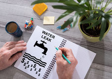 Concepto del escape del agua en una libreta imagenes de archivo