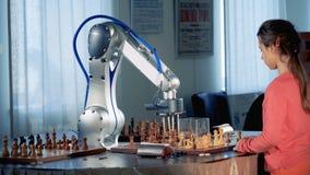 Concepto del genio del niño Chica joven elegante que juega a ajedrez con un robot moderno del ajedrez 4K almacen de video