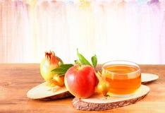 Concepto del hashanah de Rosh - miel y granada de la manzana sobre la tabla de madera Fotos de archivo