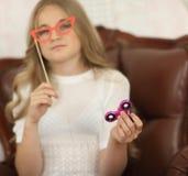 Concepto del hilandero niña que juega con el hilandero rosado y los vidrios de papel rojos en el palillo Foto de archivo libre de regalías