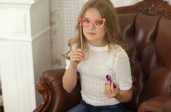 Concepto del hilandero niña que juega en casa con el hilandero rosado y los vidrios de papel rojos en el palillo Fotos de archivo