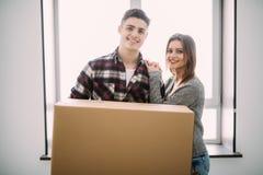 Concepto del hogar, de la gente, de la reparación y de las propiedades inmobiliarias - par sonriente con las cajas de cartón gran fotografía de archivo