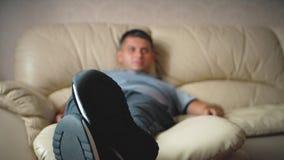 Concepto del hogar, de la gente, de la tecnología y del entretenimiento, hombre con la TV de observación teledirigida en casa almacen de video
