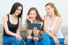 Concepto del hogar, de la tecnología y de la amistad - muchacha sonriente tres Foto de archivo libre de regalías