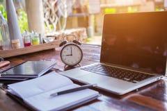 concepto del horario del negocio con el despertador negro con el cuaderno o el ordenador portátil de la pantalla en blanco en de  Fotografía de archivo