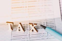 Concepto del impuesto con el bloque de madera Impuestos sobre las propiedades inmobiliarias, pago imagenes de archivo