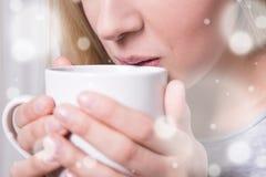 Concepto del invierno - cercano para arriba de la mujer que bebe el café o el té caliente Fotos de archivo libres de regalías