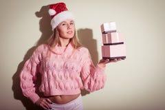 Concepto del invierno de la feliz Navidad - hembra sonriente en sombrero del ayudante de santa con muchas cajas de regalo Fotos de archivo