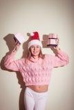 Concepto del invierno de la feliz Navidad - hembra sonriente en sombrero del ayudante de santa con muchas cajas de regalo Foto de archivo