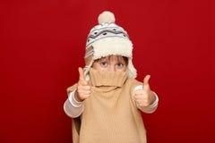 Concepto del invierno - la muchacha en sombrero y el suéter muestran el mejor gesto en fondo rojo Fotos de archivo libres de regalías