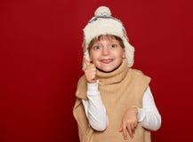Concepto del invierno - la muchacha en sombrero y el suéter muestran el pulgar en fondo rojo Imagenes de archivo