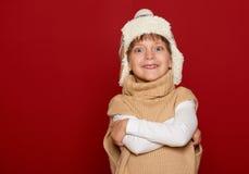 Concepto del invierno - muchacha en el sombrero y el suéter que presentan en fondo rojo Foto de archivo libre de regalías