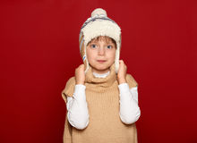 Concepto del invierno - muchacha en el sombrero y el suéter que presentan en fondo rojo Imagenes de archivo