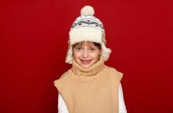 Concepto del invierno - muchacha en el sombrero y el suéter que presentan en fondo rojo Foto de archivo