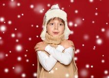 Concepto del invierno - muchacha en sombrero y suéter en fondo rojo Imagenes de archivo