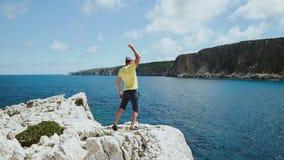 Concepto del logro Hombre atractivo que aumenta el brazo victoriosamente Salto turístico masculino encima del acantilado y celebr almacen de video