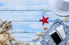 Concepto del mar de la playa del verano Fondo de madera azul con diversos accesorios, cáscaras, estrellas de mar, toalla, protecc Imágenes de archivo libres de regalías