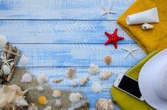 Concepto del mar de la playa del verano Fondo de madera azul con diversos accesorios, cáscaras, estrellas de mar, toalla, protecc Imagen de archivo libre de regalías