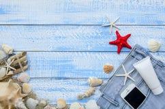 Concepto del mar de la playa del verano Fondo de madera azul con diversos accesorios, cáscaras, estrellas de mar, toalla, protecc Fotos de archivo