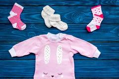 Concepto del nacimiento del niño Ropa y accesorios para recién nacido en la opinión superior del fondo de madera azul Fotos de archivo libres de regalías