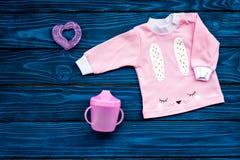Concepto del nacimiento del niño Ropa y accesorios para recién nacido en la opinión superior del fondo de madera azul Foto de archivo