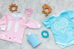Concepto del nacimiento del niño Ropa y accesorios para recién nacido en la opinión superior del fondo gris Fotografía de archivo libre de regalías