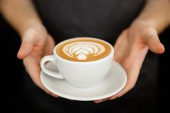 Concepto del negocio del café - cosechado cerca para arriba del café femenino de la porción con arte del latte mientras que se co imagen de archivo